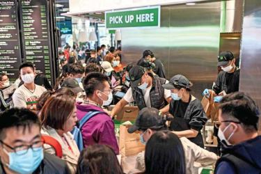 "People get their food inside a Shake Shack restaurant at a shopping mall during the national  ""Golden Week"" holiday. - AFP"