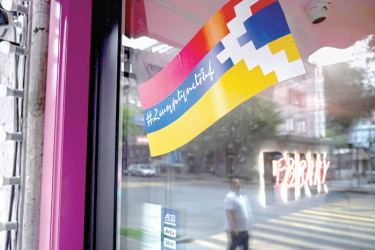 A man is reflected in the window of a barbershop decorated with a sticker-flag of the breakaway Nagorno-Karabakh region in Yerevan on October 4, 2020. - Armenian and Azerbaijani forces exchanged rocket fire as fighting intensified over Nagorno-Karabakh on October 4, with the breakaway region's capital and Azerbaijan's second-largest city bombarded. (Photo by - / AFP)