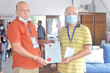 An official of the Construction Chamber presenting the certificate to the Chairman of Sampath Sofa, Sampath Fonseka.