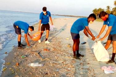 Navy troops cleaning a beach.