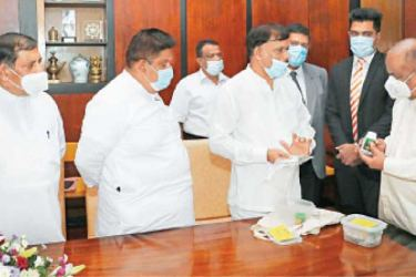 State Minister of Indigenous Medicine Promotion, Rural and Ayurvedic Hospitals Development and Community Health Sisira Jayakody presenting newly-introduced Ayurvedic drugs to Speaker Mahinda Yapa Abeywardena.