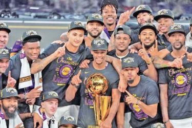 The Los Angeles Lakers celebrate with the Larry O'Brien Trophy on court after winning Game Six of the NBA Finals against the Miami Heat on October 11 in Orlando, Florida at AdventHealth Arena. AFP