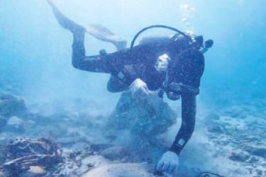 A Naval diver cleaning the sea bed.