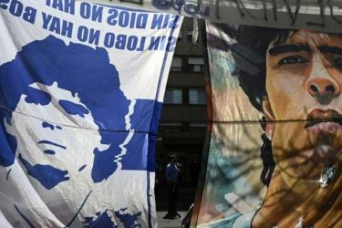 Fans of Gimnasia y Esgrima hung flags of Diego Maradona outside the clinic in La Plata, where the club is based and the football star was receiving treatment. - AFP