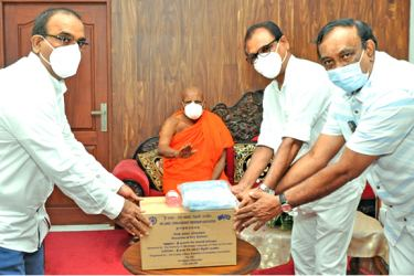 The SLCBFA donating dry rations and hand sanitizers to Most Ven Dr. Ittapane Dhammalankara Thera.