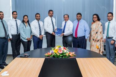 President, SLIM Roshan Fernando and Managing Director/Chief Executive Officer, MBSL Insurance Lalith Fernando, exchanging the MoU looked on by other officials