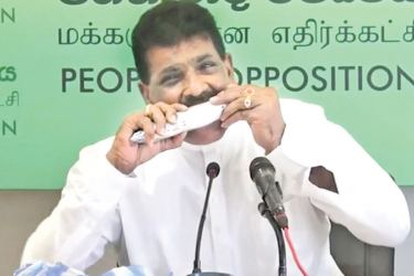 Former Fisheries Minister Dilip Wedaarachchi eats raw fish during a press conference to prove that fish is harmless.