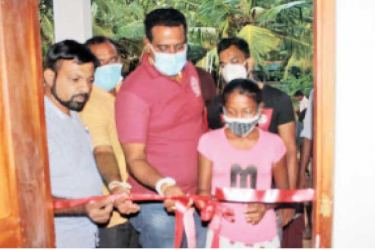 State Minister of Rural and Regional Drinking Water Supply Development Sanath Nishantha Perera opening a house that was constructed in the Puttalam District under the Gamata Geyak-Ratata Hetak housing programme.