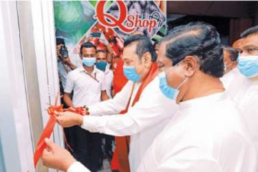 Prime Minister Mahinda Rajapaksa and Trade Minister Dr. Bandula Gunawardena opening the first 'Q-shop' at the State Commercial Corporation yesterday.