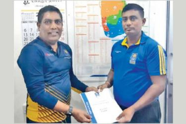 Pathmanathan Lavendra receives his level 11 coaching certificate from Heshan De Mel, head of coaching education at Sri Lanka Cricket.