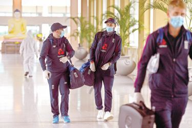 England's captain Joe Root (2R) walks along with teammates as they arrive at the Rajapaksa international airport in Mattala on January 3, 2021, as England's cricket team returned to Sri Lanka to play two Tests abandoned in March due to the Covid-19 coronavirus pandemic.  AFP