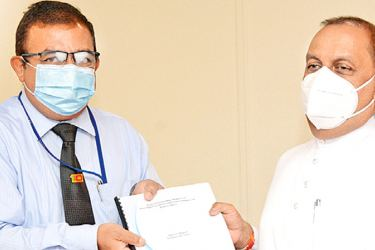 Geological Survey and Mines Bureau Chairman Anura Walpola handing over the report on earth tremors to Minister Mahinda Amaraweera.