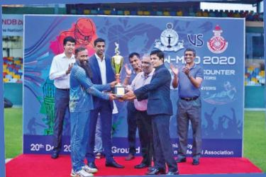 Thusith Paliwatte skipper of the victorious Lawyers XI receiving the trophy from the chief guest Jehan Mubarak