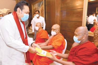 Prime Minister Mahinda Rajapaksa presenting insurance certificates to members of the Maha Sangha under the new medical insurance scheme of the Sri Lanka Insurance Corporation.