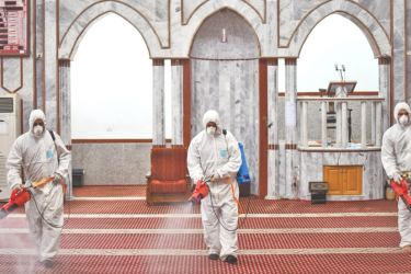 Workers disinfect a place of worship in Gaza.