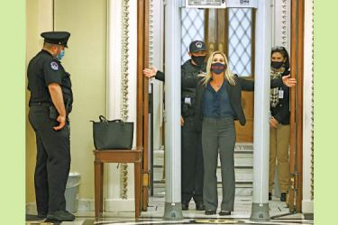 Rep. Marjorie Taylor Greene (R-GA) is searched by U.S. Capitol Police after setting off the metal detector outside the doors to the House of Representatives Chamber on Monday in Washington, DC. Metal detectors were installed at the entrances to the US House for the first time Tuesday in response to last week's riot. - AFP