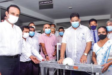 State Minister Arundika Fernando handing over a yarn machine to a recipient, while Ministers Dr. Ramesh Pathirana and Mohan P. de silva, as well as other participants, look on. Picture by Mahinda P. Liyanage, Galle Central Special Corr.