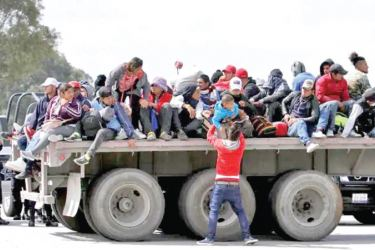 Honduran migrants sitting on a trailer trying to make to the United States.