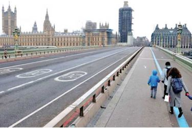 A family walks across deserted Westminster Bridge near the Houses of Parliament in London amid the COVID-19 outbreak.