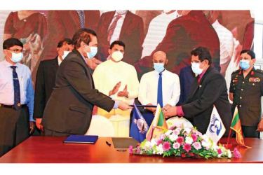 The MoU is being exchanged. State Minister Channa Jayasumana (Centre) was present.