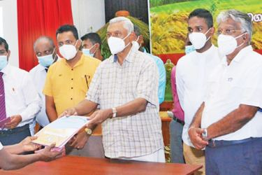 Minister Chamal Rajapaksa handing over a land deed to a Mahaweli farmer. State Minister Siripala Gamalath and officials look on.