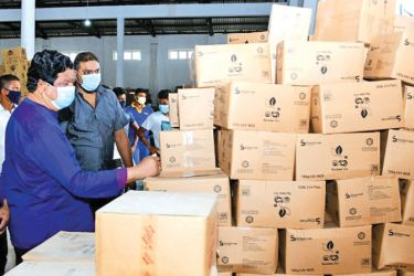 Minister Dr. Bandula Gunewardene inspecting the stock of tea packets  Picture courtesy: Trade Ministry Media Unit.