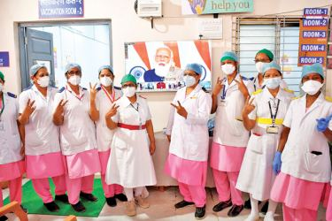 Nurses from the Rajawadi Hospital make the victory sign gesture as they pose in front of a television broadcasting a live address by India's Prime Minister Narendra Modi before the start of the COVID-19 coronavirus vaccination drive in Mumbai on Saturday. - AFP