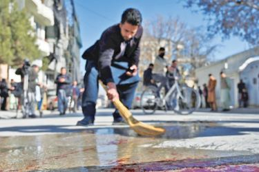 A resident washes a road after gunmen shot dead two Afghan women judges working for the Supreme Court in Kabul yesterday. - AFP