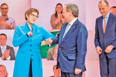 Outgoing leader of the Christian Democratic Union (CDU) Annegret Kramp-Karrenbauer (L) congratulates her sucessor North Rhine-Westphalia's State Premier Armin Laschet (C) with an elbow bump after his election as candidate for leadership Friedrick Merz (R) looks on, on the second day of the party's 33rd congress held online in Berlin on Saturday. - AFP