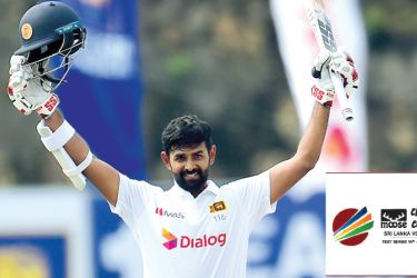 Lahiru Thirimanna raises his bat after scoring a century against England on the fourth day of the first Test at the Galle International Stadium on January 17. Picture courtesy: SLC