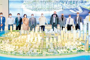 The visiting delegation observes a model of the project.