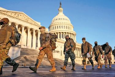 Soldiers walk past the Capitol