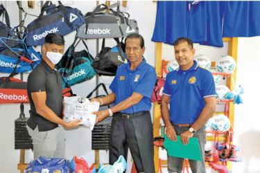 Piyadasa Perera a former National Soccer player (second from left) receives the medical package from Aaqil Rizan the LCY T-Shirts Brand Representative at their One Galle Face store yesterday. Also in the picture is Mahinda Galagedara, the founder of the project.