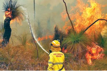 Fire crews control bushfires as they approach properties in Upper Swan in Perth on Tuesday.