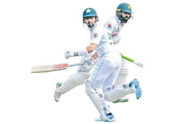 Pakistan skipper Babar Azam (L) and teammate Fawad Alam run between the wickets during the first day of the second Test match against South Africa in Rawalpindi on Thursday. - AFP