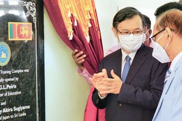 Japanese Ambassador Sugiyama Akira unveiling the complex plaque, while others look on.