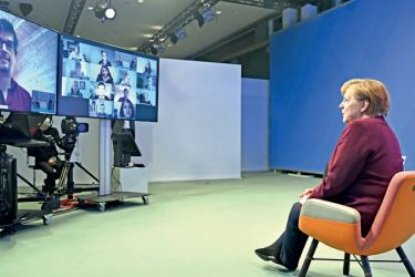 German Chancellor Angela Merkel is seen on a display as she addresses single parents during online talks as part of her citizens' dialogue series at the chancellery in Berlin on Tuesday. - AFP