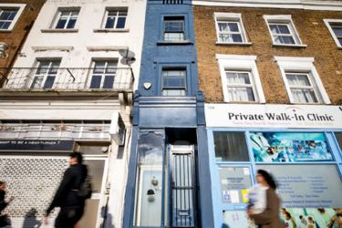People walk past the front of what is dubbed London's thinnest house (painted blue). The unusual property was built sometime in the late 19th or early 20th century. - AFP