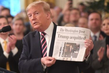 Trump holding a newspaper announcing his acquittal after the first impeachment