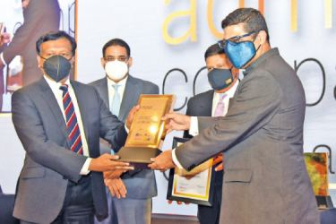 Group Managing Director/CEO of LOLC Group Kapila Jayawardena receiving the award from the Deputy High Commissioner of India Vinod K. Jacob. General Shavendra Silva, and Dinesh Weerakkody, look on.
