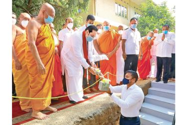 Prime Minister Mahinda Rajapaksa placing the foundation  stone of the Bodhi Wall with Prime Minister's Chief of  Staff Yoshitha Rajapaksa to begin the project. (Picture by PM's Media).