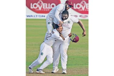 West Indies' John Campbell (top) with teammates Rahkeem Cornwall (R) and Shayne Moseley celebrate the dismissal of Bangladesh's Liton Das. - AFP