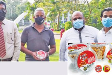 Business Development Managers, M. M.N.M. Farahad and Shafraz Salam Accounts Manager, H. F. M. Umaid presents a pack of 'Easykitchen cashew' to former Sri Lankan legendary fast bowler Chaminda Vaas
