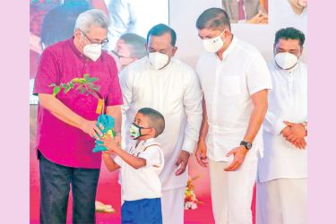President Gotabaya Rajapaksa launched the National Tree Planting Programme for Children Kekulu Tharu Udanaya at the Atabage Wimaladharma National School in Gampola yesterday. Here, the President presents a sapling to a Grade One student. (Picture courtesy President's Media Division)