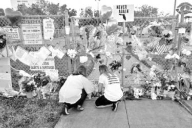 People light candles at a makeshift memorial outside Marjory Stoneman Douglas High School, where 17 students in the faculty were killed in a mass shooting in Parkland, Florida in 2018.