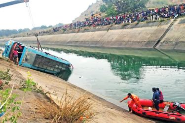 Onlookers stand along a canal as rescue teams search for survivors after a bus plunged into a canal killing at least 39 passengers in the Sidhi district of Madhya Pradesh State on Tuesday. - AFP