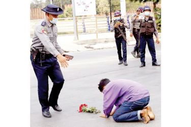 A protester offers flowers and kneels on a road before a Police officer in Mandalay, Myanmar as protests in Myanmar against the military coup that removed Aung San Suu Kyi's Government from power have grown in recent days.