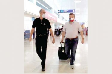 US Senator Ted Cruz (Republican -Texas) (R) walks with an unidentified person at the Cancun International Airport in Mexico before boarding his plane back to the U.S.
