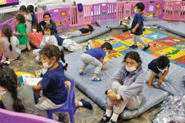 Monitored by a caretaker, young unaccompanied migrants, ages 3-9, watch TV inside a playpen at the Donna Department of Homeland Security holding facility, the main detention centre for unaccompanied children in the Rio Grande Valley in Donna, Texas.