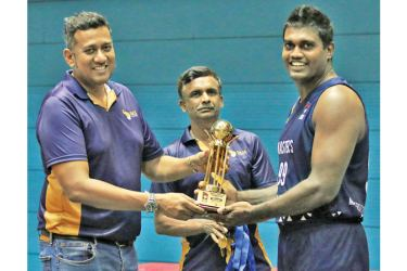 Marius Asanka Suwaris captain of team Blue receives the over 35-Trophy from Gayath Jayasinghe, CEO of Gaja Holdings-the sponsors of Masters Basketball Inter-League Tournament held recently. Also in the picture is Basil de Silva acting Secretary of MBSL